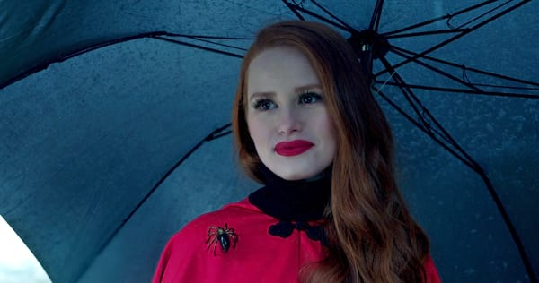 Cheryl Blossom from the TV show Riverdale stands beneath a black umbrella. She has on red lipstick, a red coat, and her signature spider broach., pop culture, movies/tv