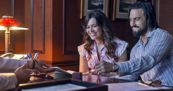 Jack and Rebecca from This Is Us sitting at a desk and looking happy., wdc-slideshow, movies/tv, pop culture