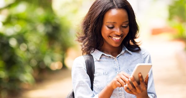 Woman smiling as she looks at her phone., wdc-slideshow, science & tech