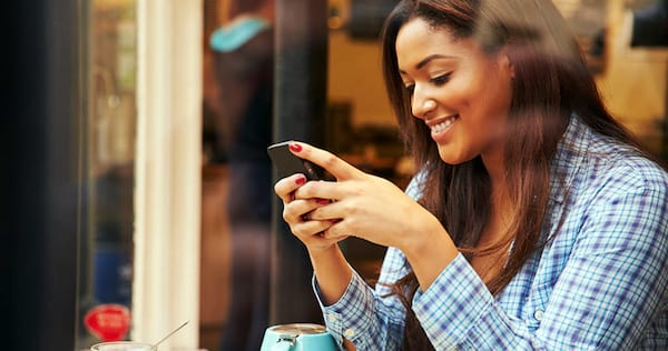 Woman looking down at her phone and smiling., wdc-slideshow, science & tech
