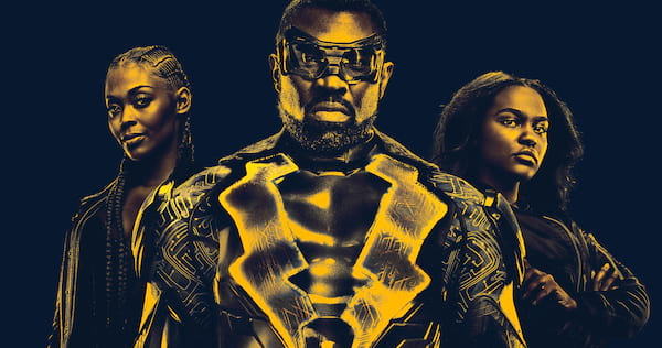 Black Lightning and his daughters, Anissa and Jennifer, standing together. The photo has a yellow tint., wdc-slideshow, pop culture, movies/tv