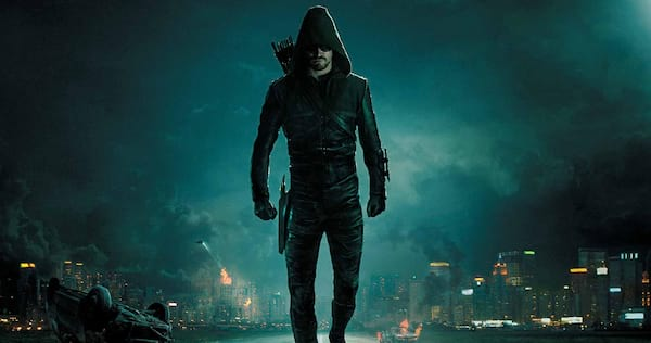 Arrow's Oliver Queen dressed as the Green Arrow. Star City is in chaos behind him., wdc-slideshow, movies/tv, pop culture