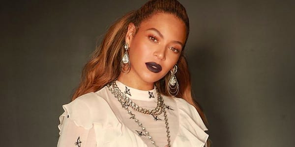 Beyoncé wearing dark lipstick and a white dress with cranes on it posing for the camera in an image posted on her Instagram account, celebs