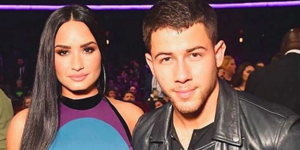 Demi Lovato and Nick Jonas posing together at an awards show, celebs