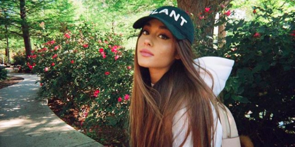 Ariana Grande in nature wearing a hat and looking sad at the camera, celebs
