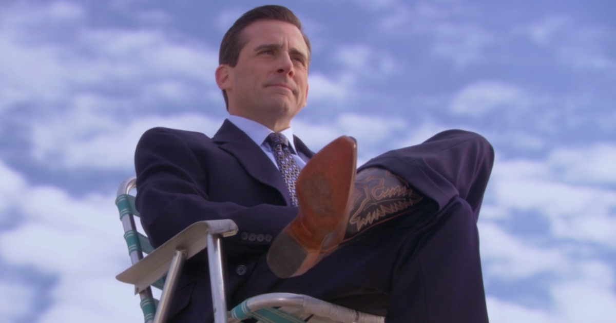 Steve Carrel as Michael Scott on an episode of The Office sitting in a lawn chair on top of the building wearing a business suit and cowboy boots with a cloudy background behind him, movies/tv