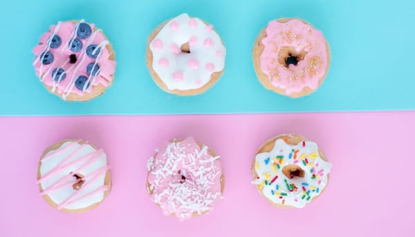 best Detroit bakery, six frosted donuts with a pink and blue background