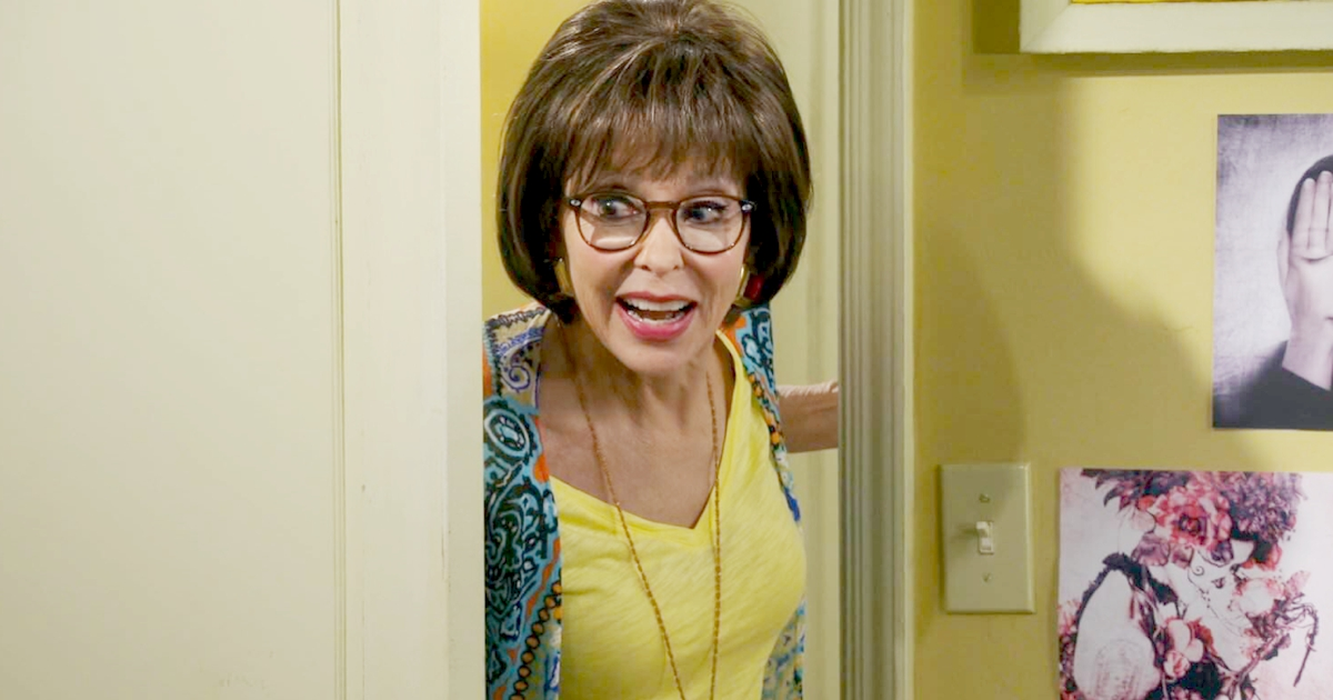 Rita Moreno as Lydia in Netflix's One Day at a Time wearing a yellow T-shirt and a floral cardigan, celebs, movies/tv