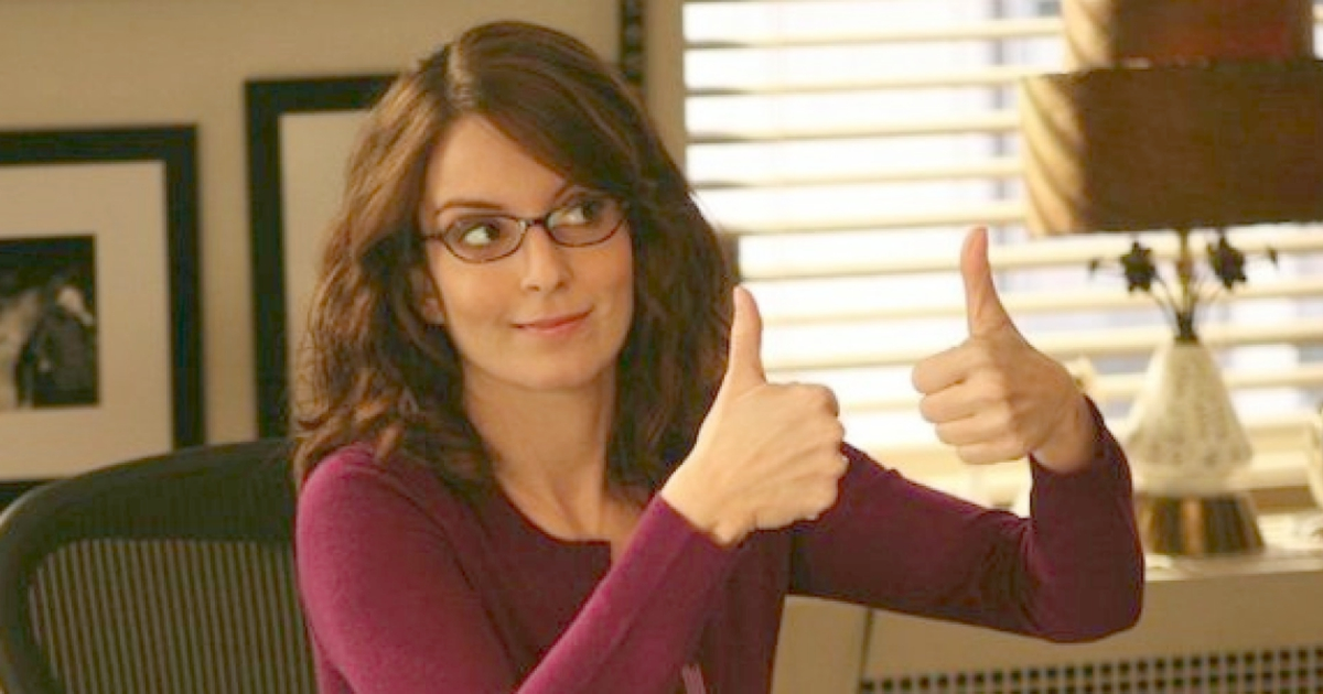 Tina Fey as Liz Lemon holding two thumbs up to someone off camera on 30 Rock, movies/tv