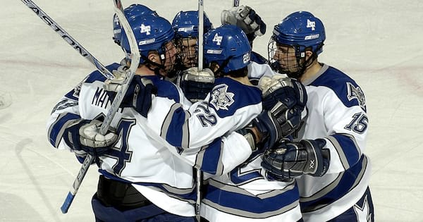 Hockey players in a huddle hugging each other after a goal