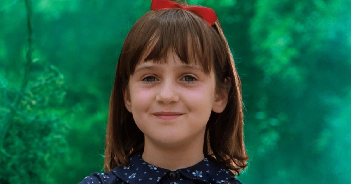 Matilda wearing a blue dress and red ribbon in her hair in Matilda