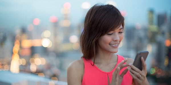Woman smiling at phone., science & tech, relationships, wdc-slideshow