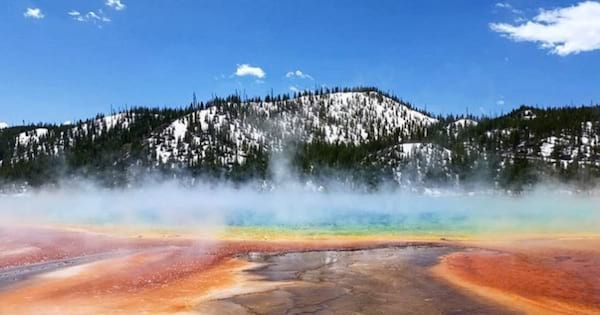 Shot of Grand Prismatic Spring in front of a snow-covered mountain in Yellowstone National Park