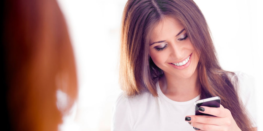 Woman smiling down at phone., science & tech, wdc-slideshow