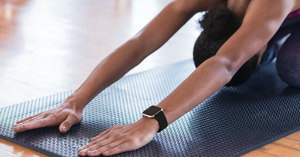Woman wearing a black/black aluminum fitbit while doing yoga