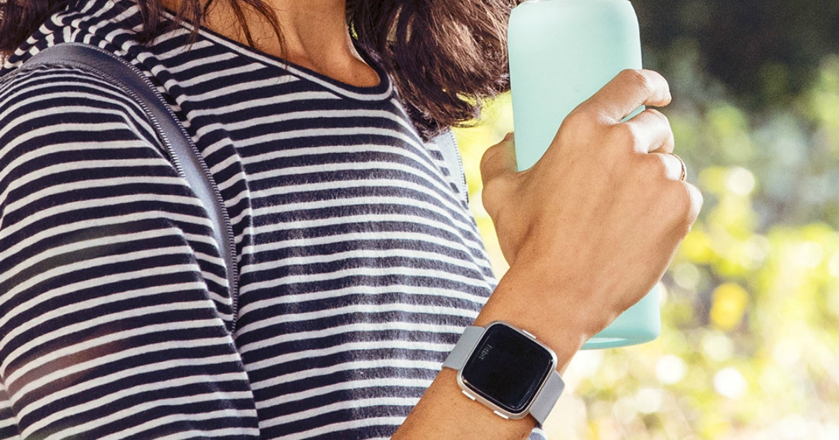Woman in a striped T-shirt wearing a gray/silver aluminum fitbit while holding a teal water bottle