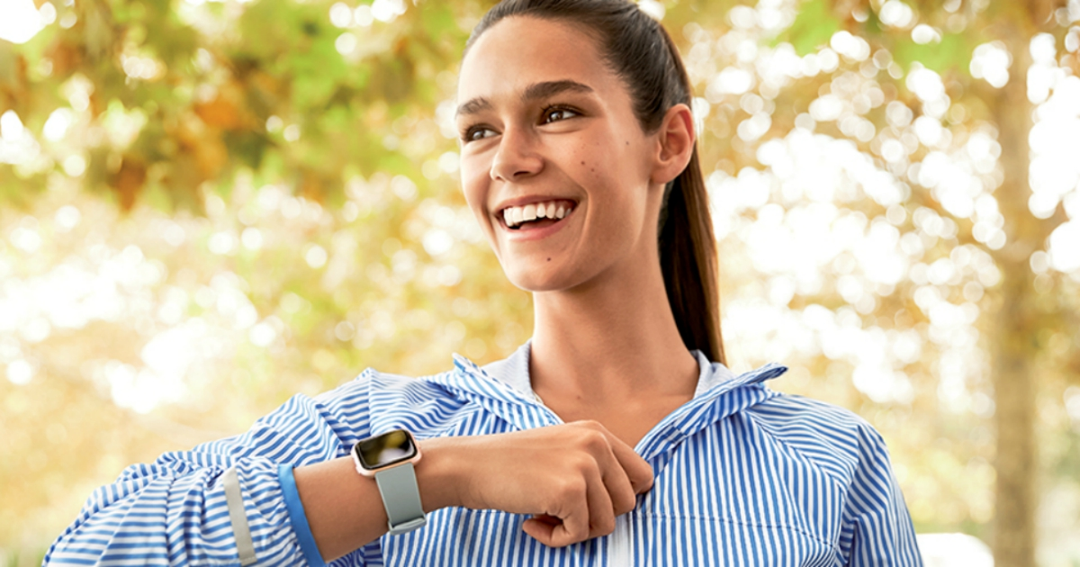 Smiling woman walking and showing off her fitbit