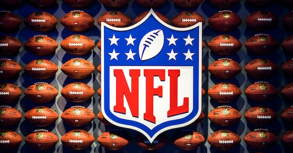 Giant NFL logo mounted in front of different footballs