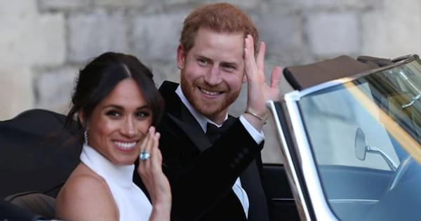 Prince Harry and Meghan Markle waving while driving off in a car