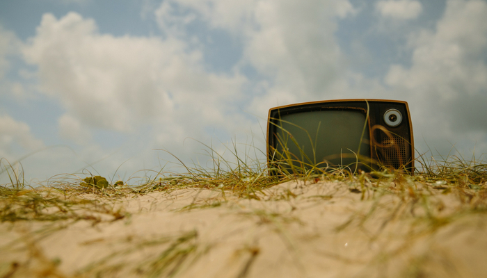 an old television sitting on the top of a sandy beach dune with a blue sky and clouds