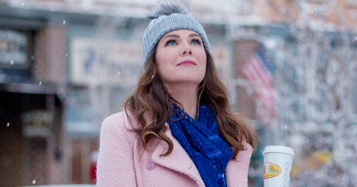 Lorelai Gilmore watching the snow fall while holding a cup of coffee