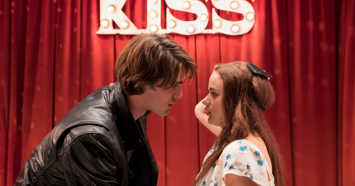 Two characters sitting under a light-up sign that reads \KISS\ about to kiss in The Kissing Booth
