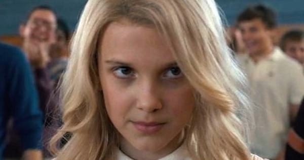 Millie Bobby Brown as Eleven in Stranger Things wearing a blonde wig, .