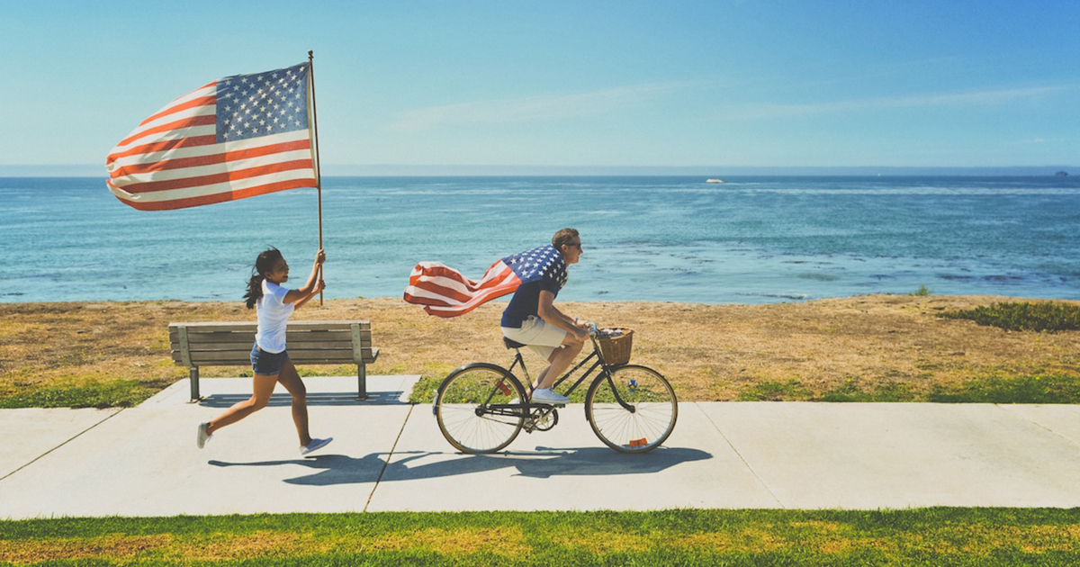 Guy riding a bike along the beach with an American flag draped around his shoulders while a girl carrying an American flag runs behind him