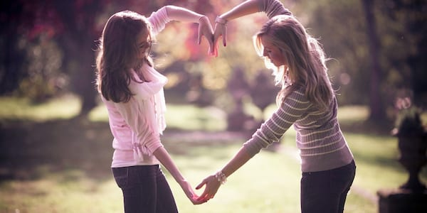 Best friends making a heart with their arms., science & tech, relationships