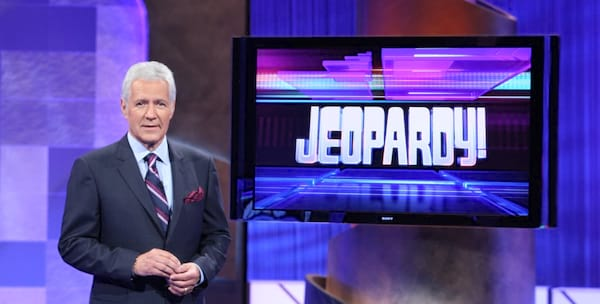 Alex Trebek standing next to a TV that says Jeopardy! on it
