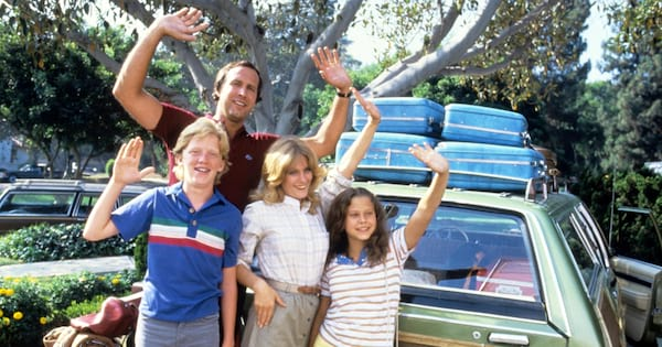 The Griswold family standing in front of a packed-up car waving goodbye to someone before heading out on a road trip