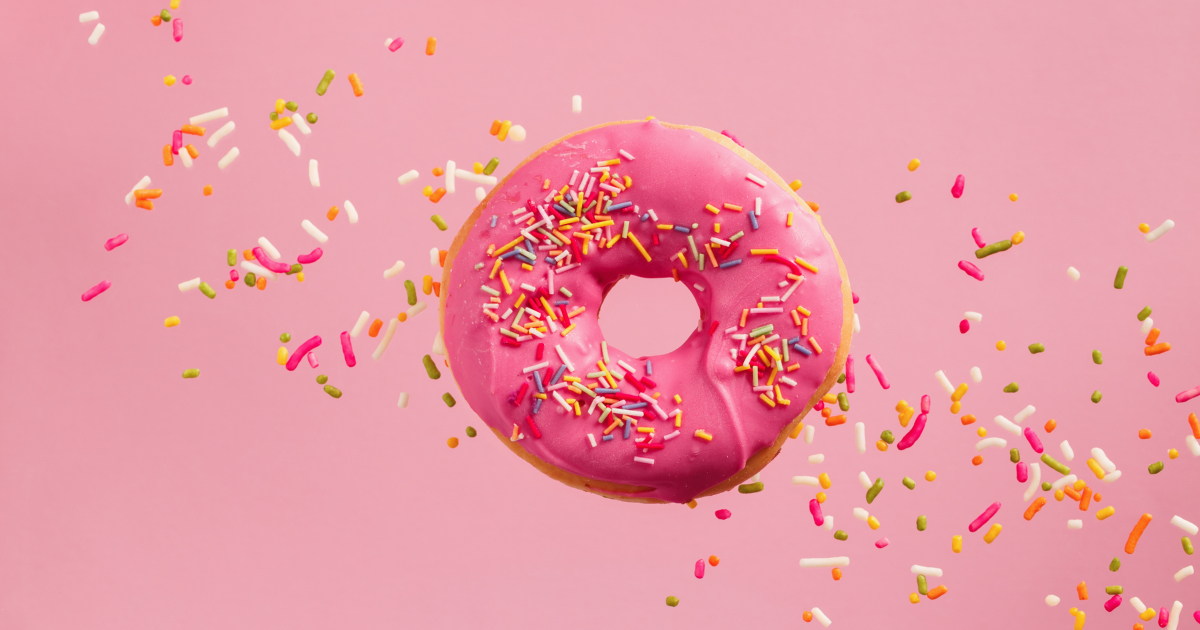 Donut with pink frosting and sprinkles floating in front of a pink background