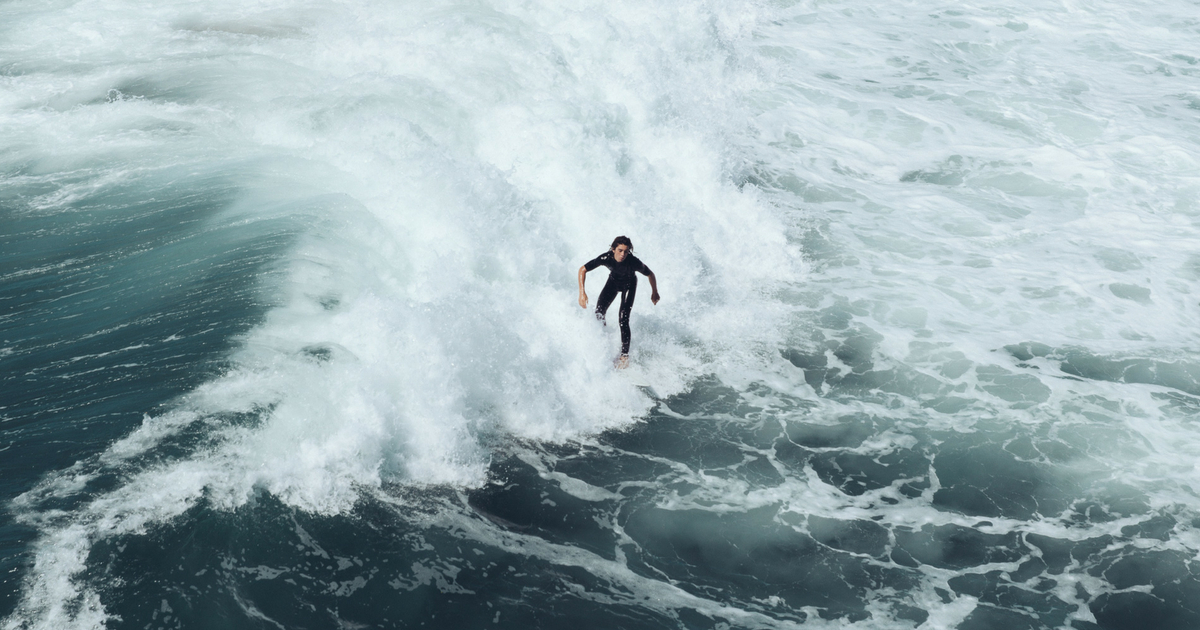 man surfing in a wet suit in white wash blue water