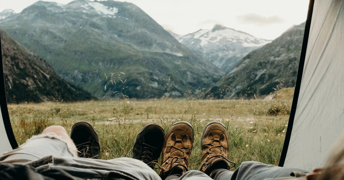 a couple camping with their feet out of the tent on grass with a view of the mountains, camping, camp