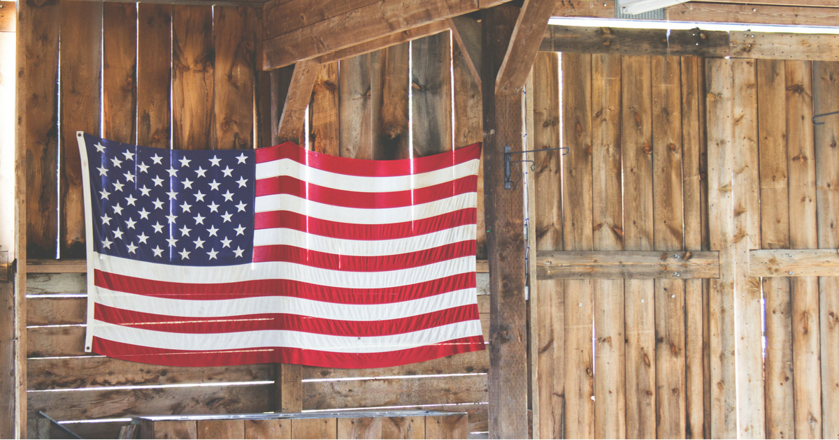 American flag hanging from a wood beamed barn
