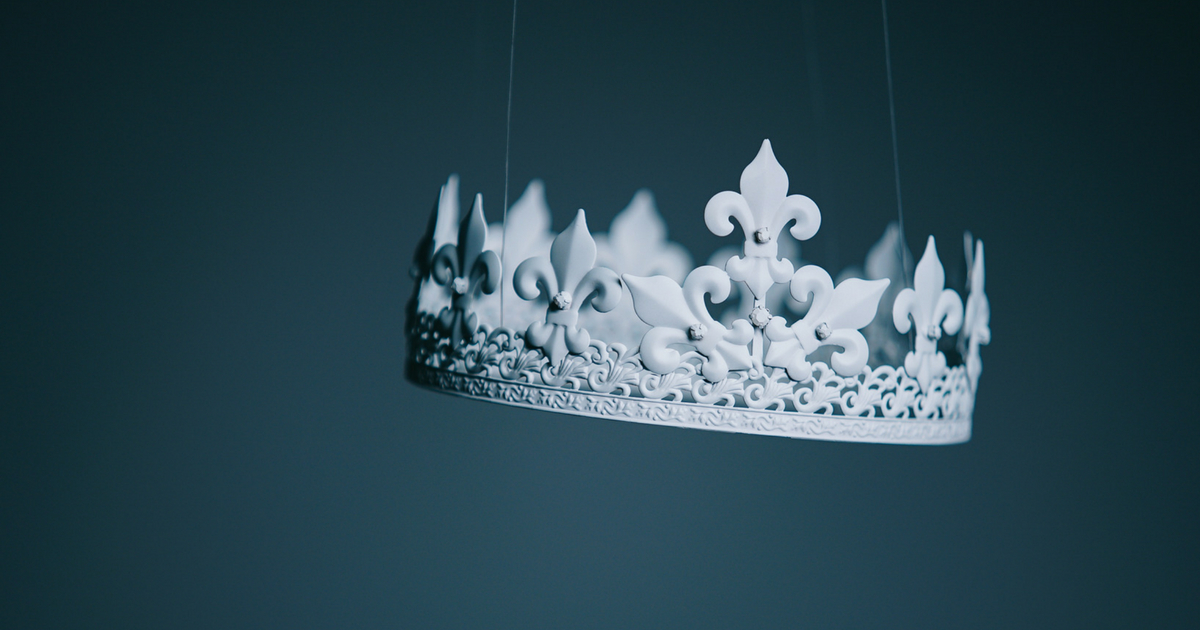 white crown hanging from clear wires in front of a dark blue/gray background