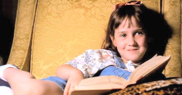 Matilda lounging in a big chair and reading a book in the movie Matilda