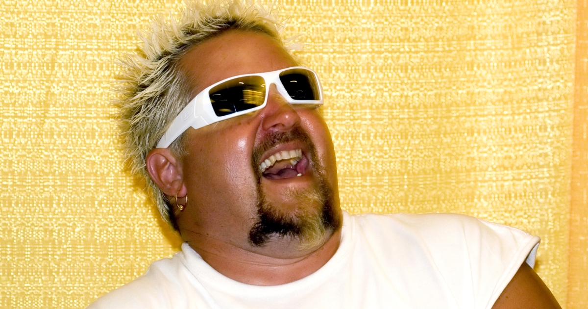 Guy Fieri wearing sunglasses and laughing in front of a yellow backdrop at a press event