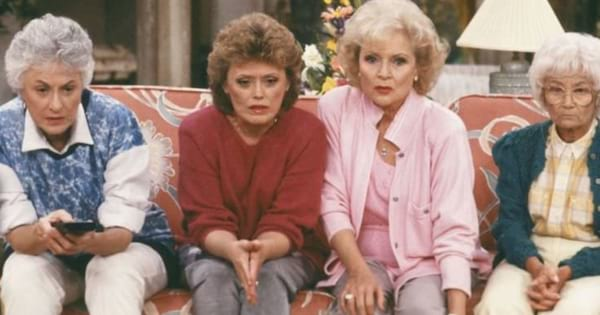 The Golden Girls sitting on a couch watching TV with shocked looks on their faces