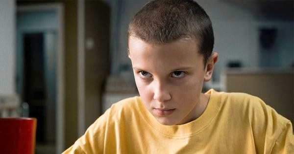 Millie Bobby Brown as Eleven in the first episode of Stranger Things wearing a yellow oversized T-shirt