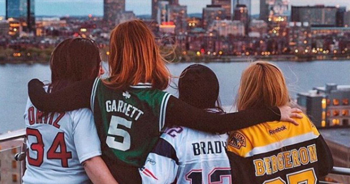 Four girls wearing Boston sports team jerseys while looking at the Boston harbor