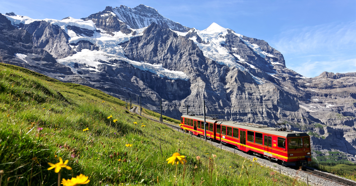 Red train on the tracks in front of a mountain landscape in Switzerland