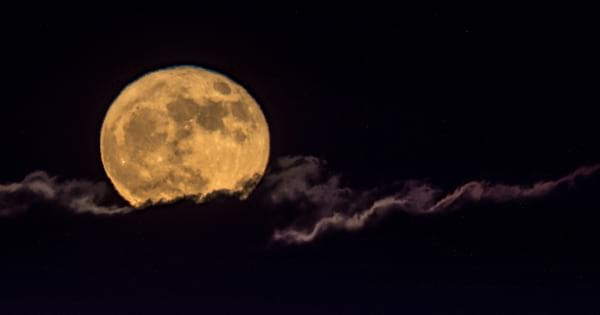 A yellow-tinted full moon in the clouds