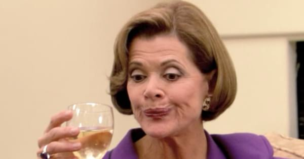 Lucille Bluth holding a glass of wine and making a sour face on Arrested Development