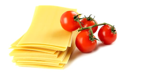 Lasagne pasta sheets next to tomatoes on a vine