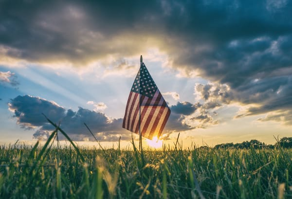 patriotic American flag in the grass with the sun setting behind it