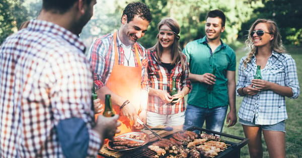 Group of friends outdoors all surrounded around a BBQ