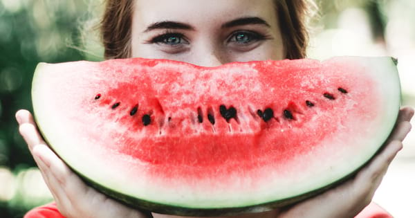 Girl hiding her smile behind a large slice of watermelon