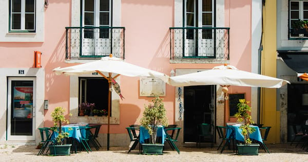 cafe chairs and table against a pink apartment building in Portugal
