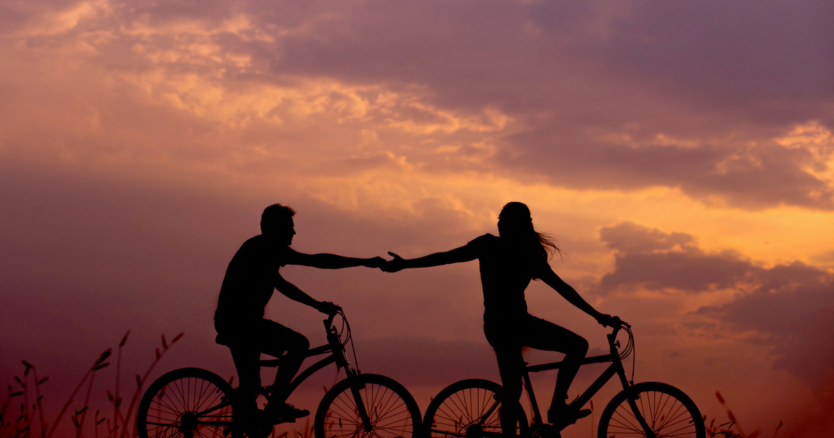 two couples riding their bikes at dusk reaching for one another